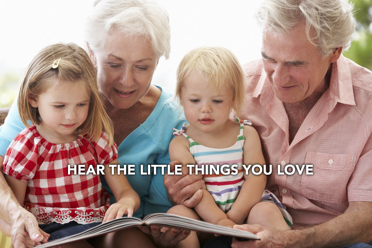 an old couple reading a book with their grandchildren